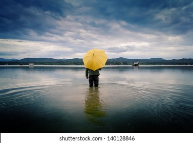 man with a yellow umbrella stands in the water of the lake