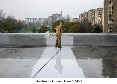 Man in yellow uniform cleaning roof top from dirt. Floor is all under water. In front of worker visible cityscape.
