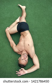 Man yoga practice pose green surface top view. Athlete doing yoga asana at green background. Practicing asana concept. Guy muscular flexible body. Training flexibility stretch muscles and joints.