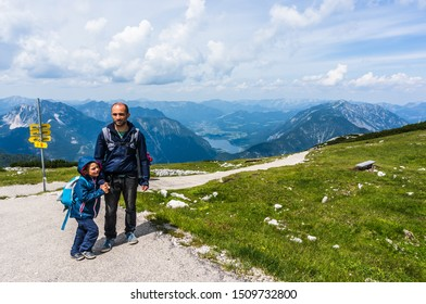 Man and young boy standing on a footpath next to a grass field on a hill with view to the Alp mountains in Dachstein on circa July 2019 in Obertraun, Austria.