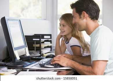 Man and young girl in home office with computer smiling