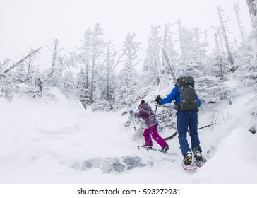A man and a young girl snowshoeing up a snowy mountain in Mont-Megantic, Quebec, Canada on Saturday, December 31, 2016.