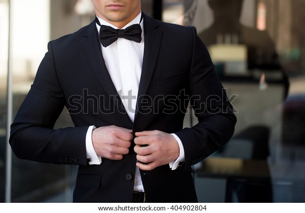 Man young handsome elegant unbuttons suit coat with bow tie at glass entrance door on urban background