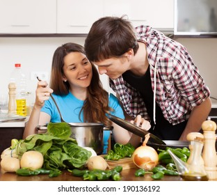 man and young woman cooking together  in kitchen