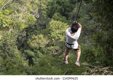 A man ziplines through the forest in Lao
