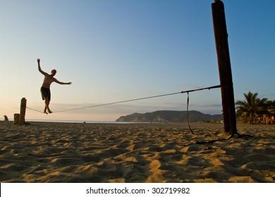 MANABI, ECUADOR - JUNE 5, 2012: Unidentified young man balancing on slackline at a beach in Manabi.
