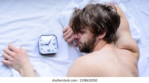 Manage proper regime tips. Oversleep problem. Toughest part of morning simply getting out of bed. Man unshaven sleepy face lay pillow alarm clock top view. Guy sleep missed alarm clock ringing.