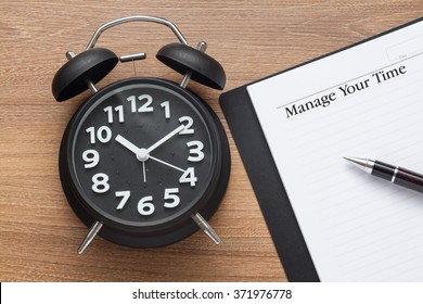 manage your time conceptual,book,pen and clock on wood