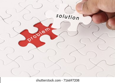 Management concept with hand holding piece of jigsaw puzzle with problem and solution wording
