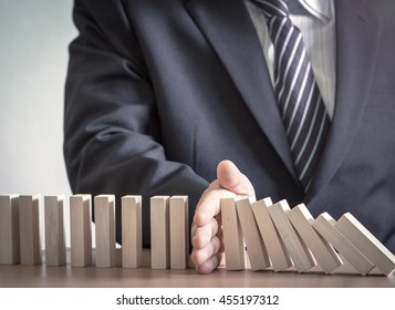 Management concept: Manager hand stopping the domino effect on office background.
