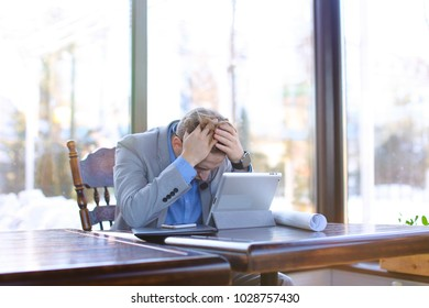 Management consultant talking with client by tablet using headset phones with microphone and sitting at cafe. Young hardworking wears grey suit and looks tired. Concept of helping to find solutions to
