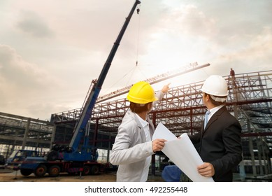 Management consulting with engineers working with hard hat and holding blueprint in his hand for management business plan.