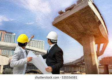 Management consulting people holding blueprint in his hand and discussion with engineers about the progress and construction planning of highway bridge in the future