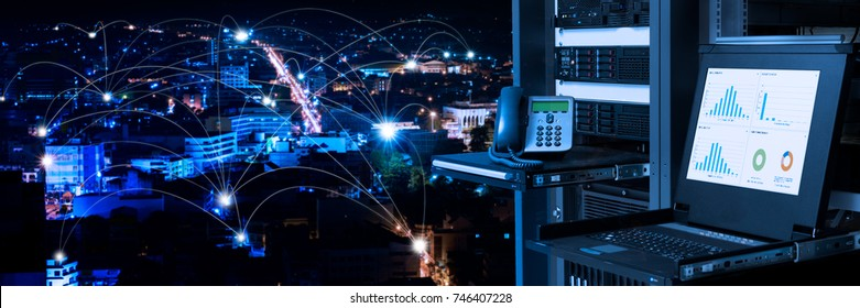 Management and monitoring monitor in data center and connectivity lines over night city background, smart city concept