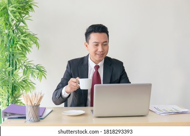 The manager of an Asian man sipping coffee on his desk in a radiant manner.