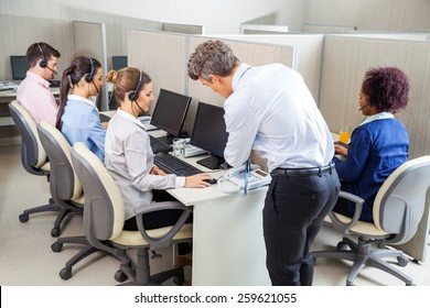 Manager assisting young female customer service agent while employees working in call center