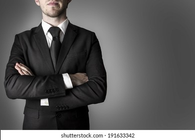 manager in black suite with crossed arms