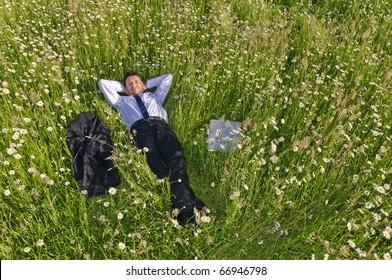 Manager, Geschäftsmann, der mitten in einem Blumenfeld liegt und entspannter, seine Jacke neben ihm