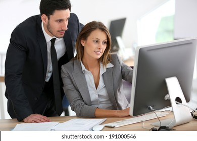 Manager with businesswoman working on desktop