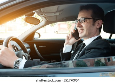 Manager calling on the phone seated in the car portrait