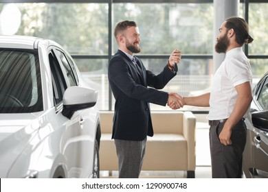 Manager of car center shaking giving keys to new owner of automobile. Happy bearded man in white shirt shaking hands with car dealer. Men smiling, standing near white auto.