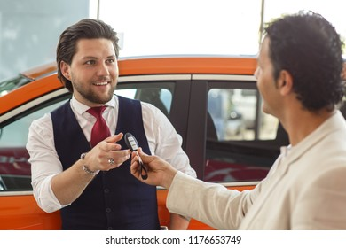 Manager of car dealership holding keys from car an hand and giving it to customer. Happy client smiling, taking keyes and looking at dealer. Process of purchasing automobile.
