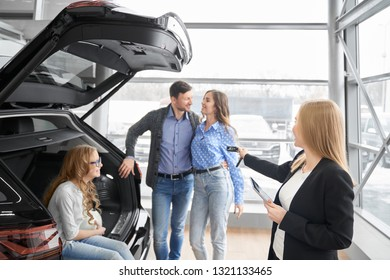 Manager of car dealership working with clients, holding folder and giving car keys to buyers of vehicle. Couple standing, posing, daughter sitting in car trunk, smiling.