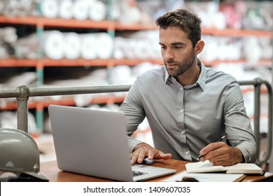 Manager checking online orders and inventory on a laptop while sitting at a desk in a carpet warehouse with shelves of stock in the background