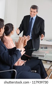 Manager clapping hands for consultant after a presentation in the office