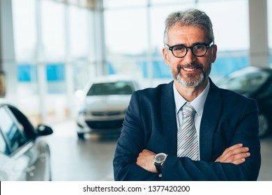 manager crossed arms in car showroom