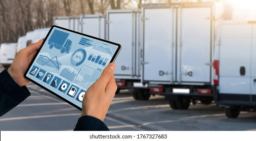 Manager mit einer digitalen Tablette auf dem Hintergrund von LKWs. Flottenmanagement