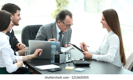 Manager discussing work issues with his assistants behind a Desk