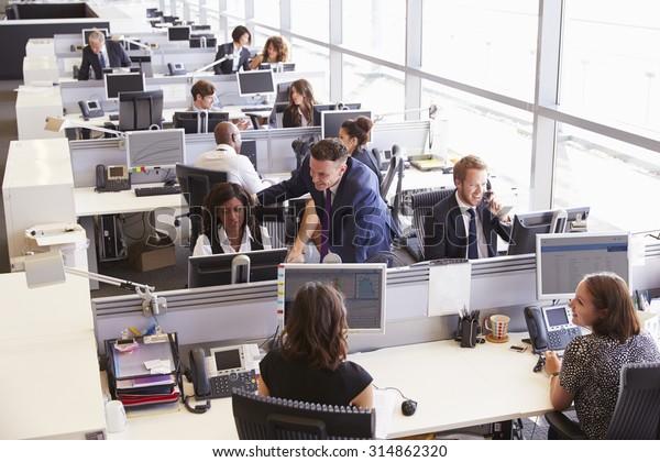 Manager in Gesprächen mit Mitarbeiter in einem offenen Planungsbüro