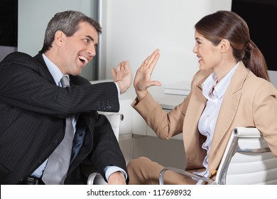 Manager and employee in the office giving high five to each other