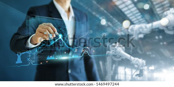 Manager engineer analyzing and control automation robot arms machine on software modern virtual interface data real time  in intelligent factory industrial and digital manufacturing operation.
