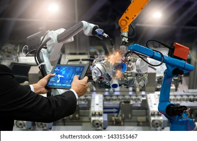 Manager engineer touch screen control automation robot arms the production of factory parts engine manufacturing industry robots and mechanical arm