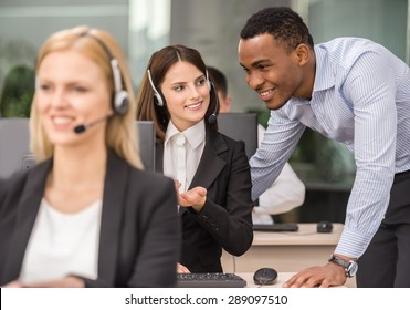 Manager explaining something to his employee in a call centre.