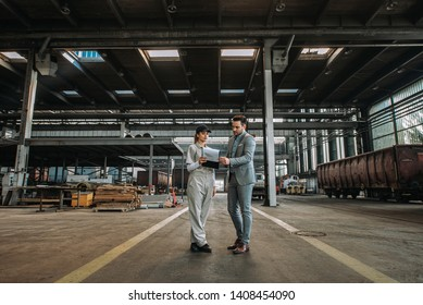 Manager and female worker talking at train factory hall.