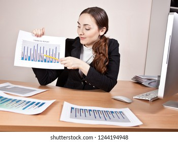 Manager with financial reports sitting at the table at the office