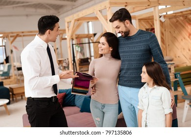 The manager of the furniture store holds samples of fabrics for furniture upholstery. Near him are a mom, dad and the girl. They are furniture buyers.