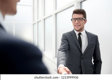 Manager greets the client with a handshake.