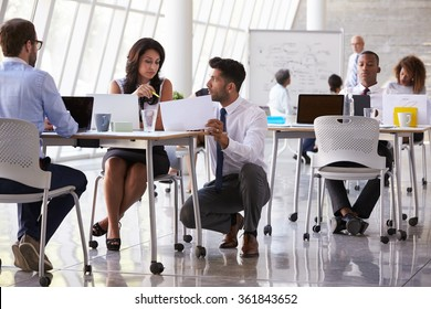 Manager Helping Staff In Busy Office Environment