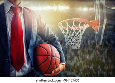 manager holding a basketball on supporters background