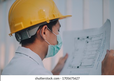 Manager holding blueprint working on construction site