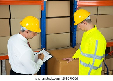 Manager Holding Clipboard Checking The Inventory With Warehouse Worker