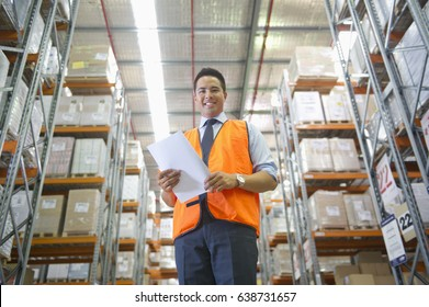 Manager holding paperwork in warehouse