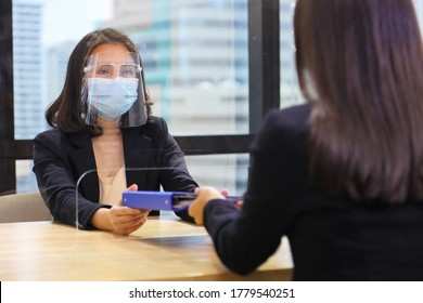 Manager from HR department wearing facial mask is interviewing new applicant who is handing her resume and profile through the partition for social distancing, transaction and new normal policy