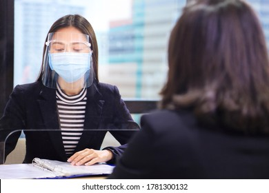 Manager from HR department wearing facial mask is interviewing new applicant and reading her resume and profile through the partition for social distancing and new normal policy