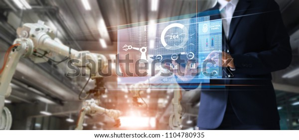 Manager industrial Engineer using tablet check and control automation robot arms machine in intelligent factory industrial over system on virtual interface screen, Industry 4.0 concept