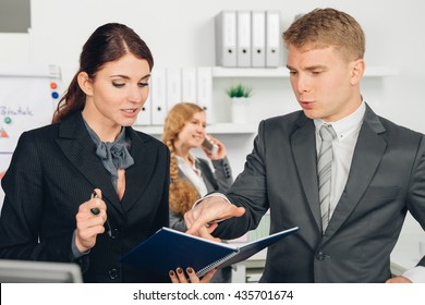manager instructs employee in office